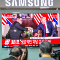 People watch a television broadcast in Seoul featuring images of U.S. President Donald Trump and North Korean leader Kim Jong Un during their summit in Singapore on June 12, 2018. | BLOOMBERG