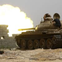 Fighters loyal to the internationally recognized Government of National Accord (GNA) open tank fire from their position in the al-Sawani area south of the Libyan capital of Tripoli during clashes against forces loyal to strongman Khalifa Hifter on Thursday. | AFP-JIJI