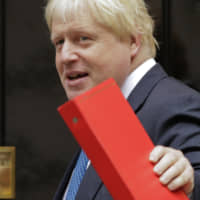 Boris Johnson, Britain's then-foreign secretary, waves to the media as he arrives for a Cabinet meeting at No. 10 Downing St. in London in October 2017. | AP