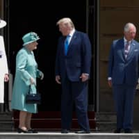 Britain's Queen Elizabeth II) speaks with U.S. President Donald Trump as U.S. first lady Melania Trump (left) stands by with Britain's Prince Charles, Prince of Wales, and Britain's Camilla, Duchess of Cornwall, in attendance during a welcome ceremony at Buckingham Palace in central London on Monday. | AFP-JIJI