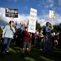 People protest outside Buckingham Palace during the state visit of U.S. President Donald Trump and first lady Melania Trump to Britain, in London Monday. | REUTERS