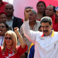 Venezuelan President Nicolas Maduro and his wife, Cilia Flores, greet people during a rally in support of the government in Caracas in May. | REUTERS