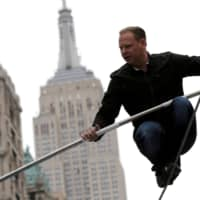 Aerialist Nik Wallenda walks a tightrope during a promotional event in Midtown Manhattan, with the Empire State Building behind him, in New York City in 2016. | REUTERS
