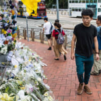 Hong Kong pro-democracy activist Joshua Wong, who was just released from jail, walks past flower tributes at a makeshift memorial site for a protester who fell to his death while hanging banners against a controversial extradition law proposal on Saturday, in Hong Kong on Monday.   AFP-JIJI
