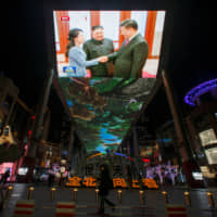 Footage showing Chinese President Xi Jinping and North Korean leader Kim Jong Un is seen on a television at a shopping mall in Beijing on Jan. 10. | REUTERS