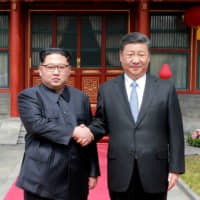 North Korean leader Kim Jong Un shakes hands with his Chinese counterpart, Xi Jinping, at the Diaoyutai State Guesthouse in Beijing in March 2018. | AP