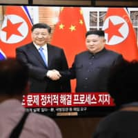 People watch a television news screen showing North Korean leader Kim Jong Un shaking hands with Chinese President Xi Jinping, at Seoul railway station in the South Korean capital on Thursday. | AFP-JIJI