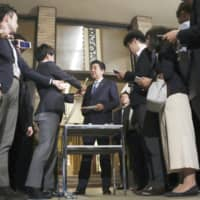 Prime Minister Shinzo Abe speaks to reporters Friday night at his office in Tokyo after a telephone conversation with U.S. President Donald Trump. | KYODO