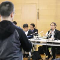 A Defense Ministry official explains errors the ministry made in its geographical survey related to the deployment of Aegis Ashore missile launchers at a meeting of local residents in the city of Akita on Saturday. | KYODO