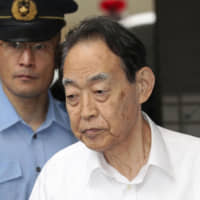 Hideaki Kumazawa, 76, is escorted out of Nerima Police Station in Tokyo on Monday morning to be sent to prosecutors. | KYODO