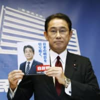 Liberal Democratic Party policy chief Fumio Kishida displays an election campaign pledge booklet for the Upper House election set for this summer on Friday at the party's head office in Tokyo. | KYODO