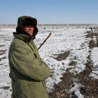 A shepherd tends his flock to the frozen fields of China's northern Heilongjiang province in February 2006. China plans to build a pilot small-scale nuclear reactor that could replace coal or gas to heat towns and cities the colder northern regions. | BLOOMBERG