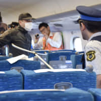 A security guard tries to subdue a knife-wielding man in the aisle of a bullet train car during a drill conducted by JR Central in August 2018. | KYODO