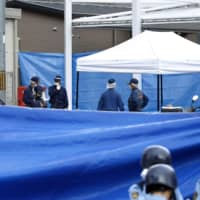 Investigators seal off the area around a police station in Suita, Osaka Prefecture, on Sunday morning hours after a police officer was stabbed and his pistol stolen. The suspect is still at large. | KYODO