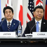 U.S. President Donald Trump, Prime Minister Shinzo Abe and Chinese President Xi Jinping attend a trilateral meeting at the Group of 20 summit Friday in Osaka. | AFP-JIJI
