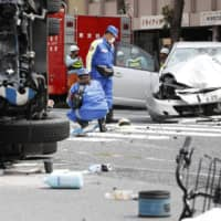 Police investigate an accident in April in which a car driven by an elderly man struck pedestrians and a garbage truck in Tokyo's Ikebukuro district, killing two people. | KYODO