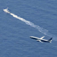 A U.S. military plane and a Japan Coast Guard boat search for a missing Air Self-Defense Force F-35A fighter jet on April 10 after it crashed in the Pacific off Aomori Prefecture during an exercise the previous day. | KYODO