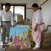 Akiyoshi Fushimi and his wife, Teru, carry a painting of hollyhocks into a new housing unit for evacuees in the town of Okuma, Fukushima Prefecture, on June 1. | FUKUSHIMA MINPO