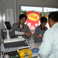 Takashi Akama, manager of the Yamazaki Shop in the town of Okuma, Fukushima Prefecture, helps out a customer on the convenience store's opening day on June 3. | FUKUSHIMA MINPO