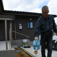 Shigeru Niitsuma, who just moved into disaster-relief housing, waters his garden in the town of Okuma, Fukushima Prefecture, on June 1. | FUKUSHIMA MINPO