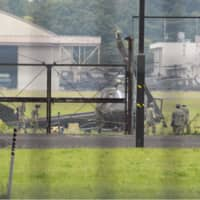 A Ground Self-Defense Force helicopter is seen after a crash landing at a camp in the suburbs of Tokyo on Friday. | KYODO