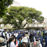 Police officers and demonstrators gather near the Atomic Bomb Dome in Hiroshima in August 2013, to commemorate the atomic bombing of the city. | KYODO