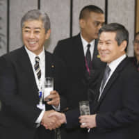 Defense Minister Takeshi Iwaya (left) and his South Korean counterpart, Jeong Kyeong-doo, shake hands during a luncheon at the Asia Security Summit in Singapore on Saturday. | KYODO