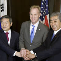 South Korean Defense Minister Jeong Kyeong-doo (left), Acting U.S. Defense Secretary Patrick Shanahan and Defense Minister Takeshi Iwaya pose for photos before beginning their trilateral meeting in Singapore on Sunday. | KYODO