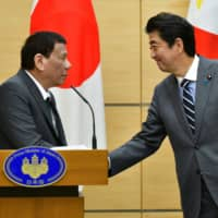 Philippine President Rodrigo Duterte greets Prime Minister Shinzo Abe during a joint press statement in Tokyo on Friday. | REUTERS