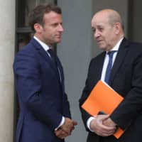French President Emmanuel Macron (left) speaks with Foreign Affairs Minister Jean-Yves Le Drian on the doorsteps of the Elysee presidential palace after a guest's departure on Monday in Paris. | AFP-JIJI