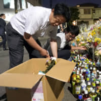 School officials of Caritas Elementary School attend to offerings made to the victims of a mass stabbing at the crime scene in Kawasaki last week. | KYODO