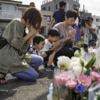 People pray at the site of a mass stabbing in Kawasaki on Tuesday, a week after the attack. | KYODO