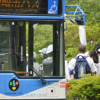 Students of Caritas Elementary School board a chartered public bus in Kawasaki on Wednesday, when the school reopened following the May 28 attack on children waiting for a school bus. | KYODO