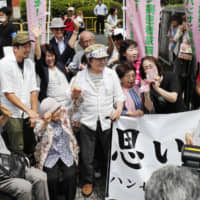 Supporters of a lawsuit demanding the payment of damages to family members of former leprosy patients applaud in front of the Kumamoto District Court on Friday after the court ordered the state to pay about ¥370 million in damages. | KYODO