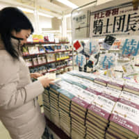 A woman looks at a copy of 'Killing Commendatore' by Haruki Murakami at a bookstore in Chuo Ward, Tokyo, shortly after it was released in 2017. | KYODO