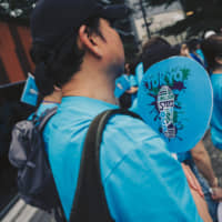 A participant of the OCD Walk held in Shibuya Ward, Tokyo, on June 2 holds a fan with a logo of the event. | DAISUKE ENOKI