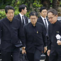 Prime Minister Shinzo Abe and Okinawa Gov. Denny Tamaki (right) arrive for an annual memorial ceremony Sunday marking the 74th year since the end of the Battle of Okinawa at the Peace Memorial Park in the city of Itoman.   KYODO
