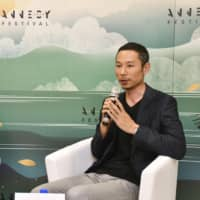 Studio Ponoc CEO Yoshiaki Nishimura speaks at a news conference in Annecy, France, on Monday as Francis Gabet, director of the Olympic Foundation for Culture and Heritage, looks on. | KYODO