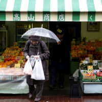 An elderly woman exits from a greengrocer's in Tokyo's Sugamo district, an area popular with retired people. | REUTERS