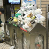 Garbage cans at a Tokyo station overflow with plastic bags in February 2018. | KYODO