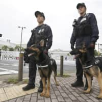 Officers with police dogs patrol around the venue of the Group of 20 summit in Osaka on Thursday, a day before the meeting begins. | KYODO