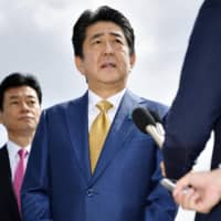 Prime Minister Shinzo Abe speaks to reporters at Haneda airport in Tokyo on Thursday before leaving for the Group of 20 summit in Osaka. | KYODO