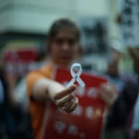 Mandy Tang, a 19-year-old exchange student from Hong Kong, shows a white ribbon during a protest rally in Tokyo on Thursday. The ribbon symbolizes support for those protesting in Hong Kong against a controversial extradition bill. She spent the night before the protest folding nearly a hundred ribbons.   RYUSEI TAKAHASHI