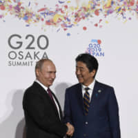 Prime Minister Shinzo Abe greets Russian President Vladimir Putin at the Group of 20 summit in Osaka on Friday.   AP