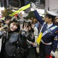 People in costumes celebrate Halloween on Shibuya crossing on Oct. 31 as a police officer tries to help control the crowd. | KYODO