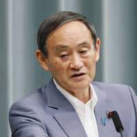 Chief Cabinet Secretary Yoshihide Suga briefs reporters at a news conference on Monday. | KYODO