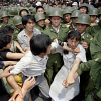 A young woman is caught between civilians and Chinese soldiers who were trying to remove her from an assembly near the Great Hall of the People in Beijing, on June 3, 1989. | AP