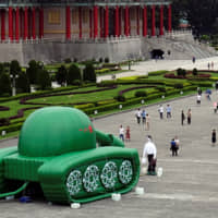 Giant balloons in the shape of a Chinese military tank and Tank Man are placed at Liberty Square, ahead of the June 4 anniversary of a military crackdown on pro-democracy protesters in Beijing's Tiananmen Square, in Taipei on May 21. | REUTERS