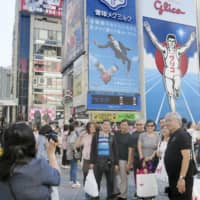 Foreign tourists pose for a photo in the Dotonbori district in the city of Osaka in October 2018.   KYODO