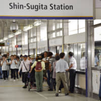 Passengers disembark and board a train at Yokohama Seaside Line Co.'s Shin-Sugita Station in Yokohama on Tuesday as automated trains resumed services, with drivers in control, three days after an accident involving one of the trains. | KYODO